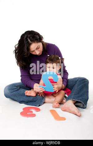 Mère, nounou, ou enseignant qui bébé à apprendre à compter un, deux, trois, avec les chiffres de manière ludique, tout en étant assis sur le plancher. Banque D'Images