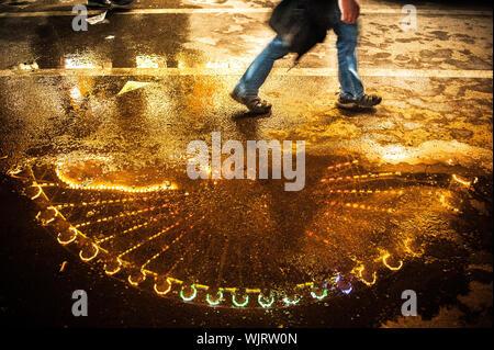 La section basse de l'homme marche sur route mouillée dans la nuit Banque D'Images