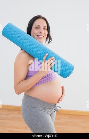 Pregnant woman holding exercise mat smiling at camera dans un studio de remise en forme Banque D'Images