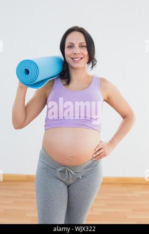 Happy pregnant woman holding exercise mat smiling at camera dans un studio de remise en forme Banque D'Images