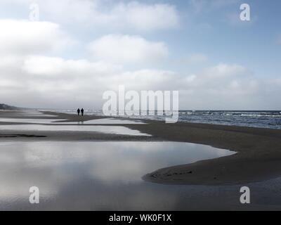 Vue éloignée sur ossature personnes marchant sur la mer contre le ciel Banque D'Images