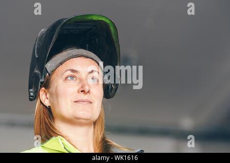 Travailleur féminin portant masque de soudage