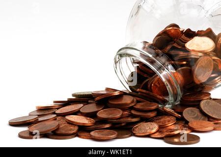 Close-up of Coins Spilling de Jar sur fond blanc Banque D'Images
