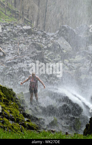 Woman Standing Under Waterfall Banque D'Images