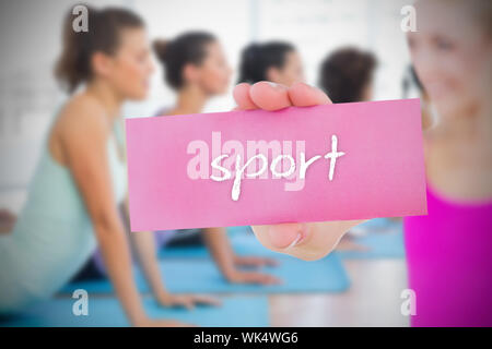 Monter blonde holding card disant sport contre yoga class in gym Banque D'Images