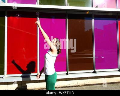 Jeune femme vers Bubble debout par bâtiment coloré Banque D'Images