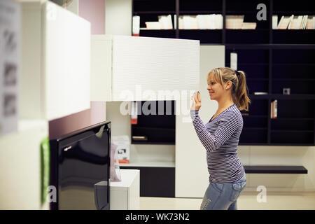 Young hispanic woman shopping for mobilier, canapé et décoration en magasin Banque D'Images