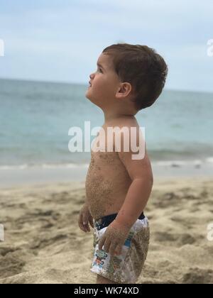 Vue latérale du torse nu Baby Boy Standing At Beach Against Sky Banque D'Images