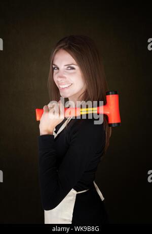 Jolie jeune femme en blouse tenant une mallet Banque D'Images