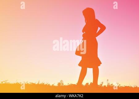 Silhouette Woman Holding Bag en se tenant sur le terrain pendant le coucher du soleil Banque D'Images