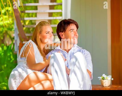Cute couple heureux s'amuser en plein air, assis sur des transats sur le luxe tropical resort, journée ensoleillée, romantique des vacances d'été, l'amour concept Banque D'Images