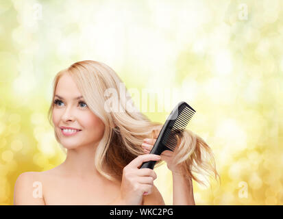 Femme souriante avec brosse à cheveux Banque D'Images