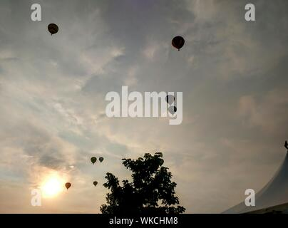 Low Angle View Of Hot Air Balloons Against Sky pendant le coucher du soleil Banque D'Images