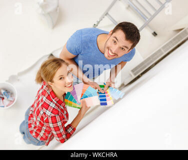 Smiling couple looking at échantillons de couleur à la maison Banque D'Images