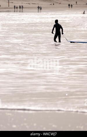 Promenades à travers l'homme tirant sa planche de surf en shore Banque D'Images