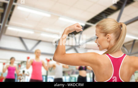 Femme sportive montrant ses biceps Banque D'Images