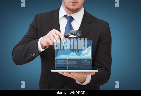 La technologie, internet et concept d'affaires - businessman holding loupe sur tablet pc ordinateur avec tableau de croissance Banque D'Images
