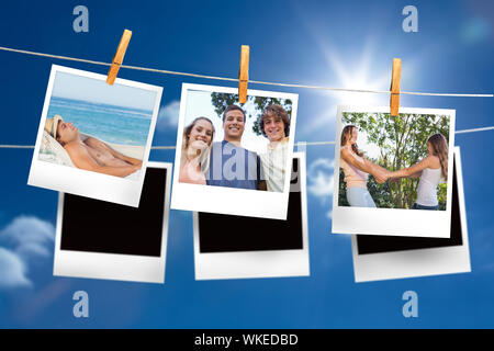 Image composite de instant photos accroché sur une ligne contre le ciel bleu Banque D'Images