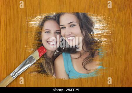 Image composite d'amis smiling at camera avec le pinceau imbibé de rouge contre table en pin en bois Banque D'Images