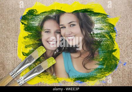 Image composite d'amis smiling at camera avec le pinceau trempé dans le jaune contre la surface altérée Banque D'Images