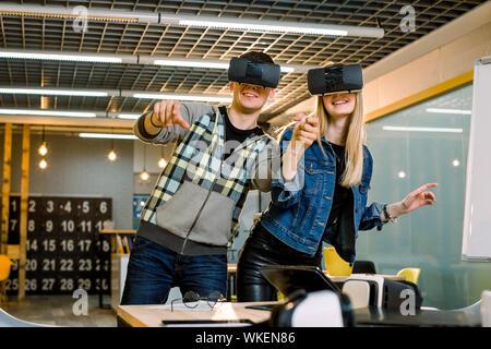 Les jeunes gens de race blanche l'homme et la femme porter des lunettes de réalité virtuelle. meilleurs amis couple having fun en utilisant les nouvelles technologies à l'essai connexion lunettes vr Banque D'Images