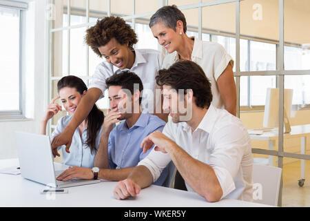 Rire des travailleurs tout en regardant dans le bureau pour ordinateur portable Banque D'Images