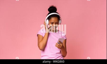 Jeune fille noire à l'écoute de la musique sur smartphone, en utilisant un casque sans fil Banque D'Images