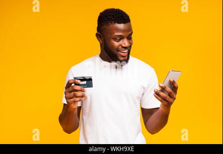 Cheerful homme noir à l'aide de carte de crédit et l'achat en ligne pour smartphone Banque D'Images