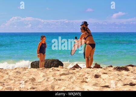 Un couple prendre une photo sur un smartphone, à l'aide d'un réflecteur de lumière, de leur fille sur la plage tout en en vacances aux Bermudes.