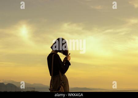 Silhouette de femme debout contre le ciel au coucher du soleil Banque D'Images