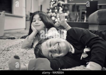 Frères et sœurs allongé sur le tapis à la maison Banque D'Images