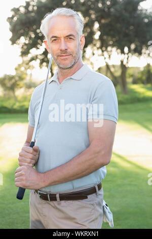 Handsome Smiling at camera golfeur sur une journée ensoleillée sur le terrain de golf