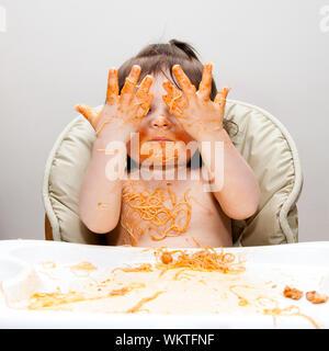 Happy Baby s'amuser manger désordonné montrant les mains couvertes de cheveux d'Ange rouge Spaghetti Pâtes marinara sauce tomate. Banque D'Images