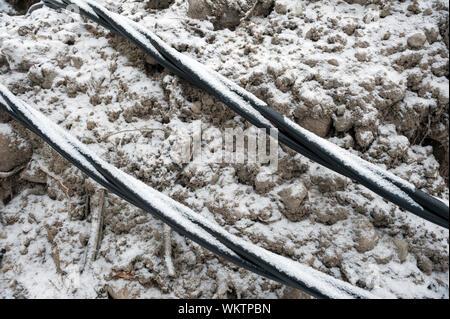 La pose d'une fibre optique et les câbles de l'électricité dans le sol gelé, câbles enterrés pour un accès internet rapide en région rurale - câbles souterrains en Finlande Banque D'Images
