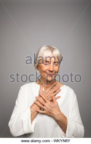 Magnifique Portrait serein, senior woman with hands over coeur Banque D'Images