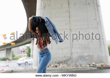 Jeune femme tenant un temps de pluie veste en jean Banque D'Images