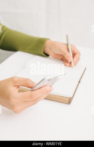 Portrait Of Businesswoman Holding Mobile Phone pendant l'écriture de journal à 24