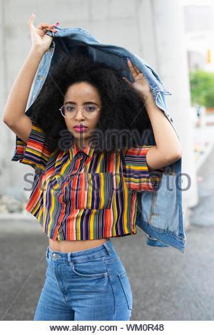 Portrait confiant, cool Jeune femme tenant un temps de pluie veste en jean Banque D'Images