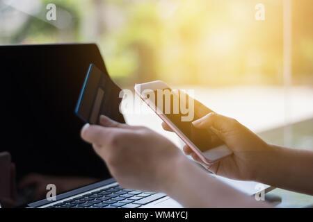 Portrait de mains tenant la carte de crédit et Téléphone sur ordinateur portable Banque D'Images