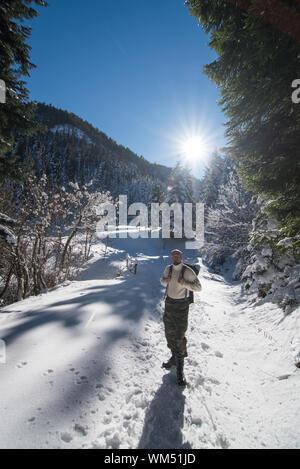Homme debout sur le terrain couvert de neige contre le ciel Banque D'Images