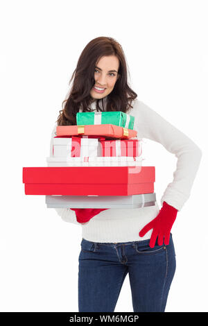 Jolie brunette posing and holding pile de cadeaux sur fond blanc Banque D'Images