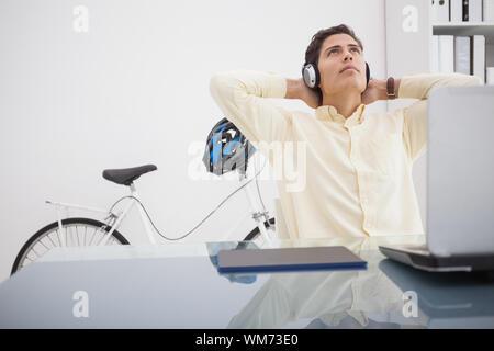 Concepteur détendue se penchant en arrière sur sa chaise dans son bureau Banque D'Images