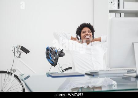 Concepteur détendue avec des écouteurs en se penchant en arrière sur sa chaise dans son bureau Banque D'Images