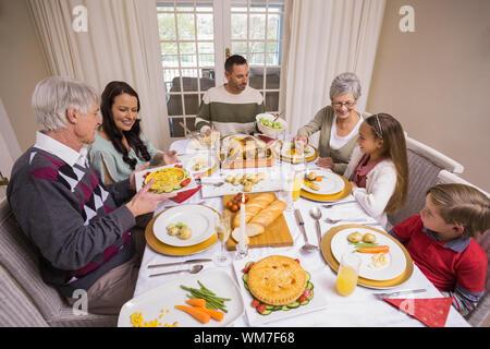 Three generation family having christmas dinner ensemble à la maison dans le salon Banque D'Images
