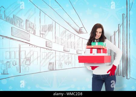 Jolie brunette posing and holding pile de cadeaux contre Motif flocon de papier peint Banque D'Images