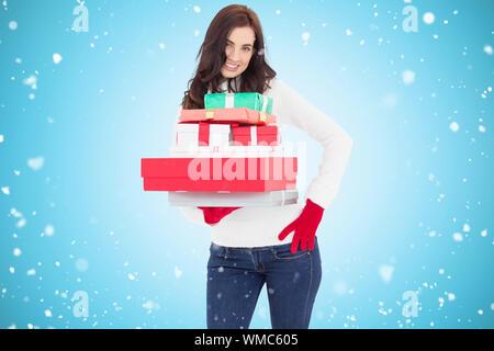 Jolie brunette posing and holding pile de cadeaux contre vignette bleue Banque D'Images