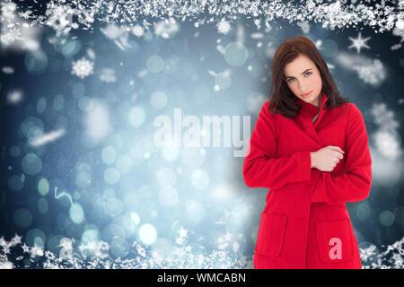 Belle brune en robe rouge posant contre blue abstract design spot lumineux Banque D'Images