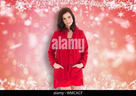 Portrait de belle brune en robe rouge et son manteau contre red abstract design spot lumineux Banque D'Images