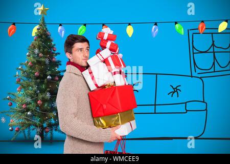 Jeune homme avec de nombreux cadeaux de noël contre fond bleu avec vignette