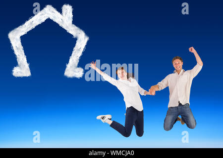 Image composite du couple jumping and holding hands against blue sky Banque D'Images